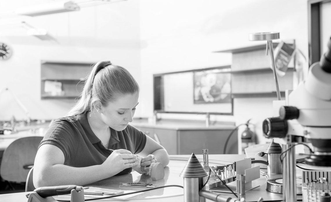 Feinarbeit in der Zahntechnik: Eine junge Mitarbeiterin bei der Fertigstellung eines Implantats