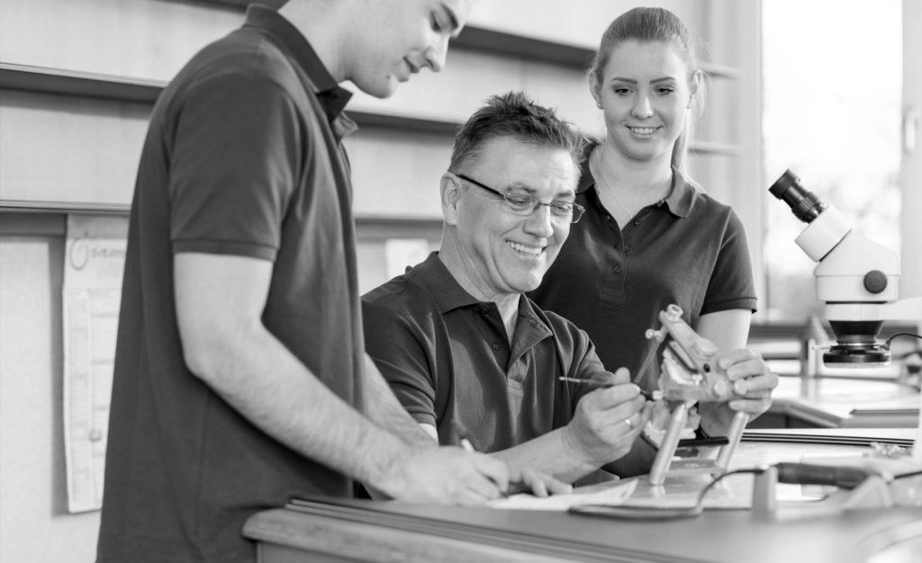 Zahntechniker Rainer Fehling arbeitet zusammen mit seinen jungen Mitarbeitern an einer Zahnprothese