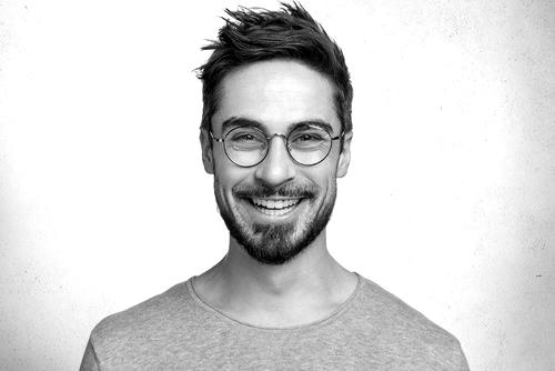Ein zufriedener junger Mann lächelt